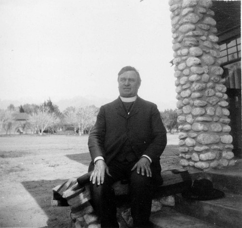 Father Benedict Florian Hahn of the St. Boniface Indian/Industrial School sitting on porch of the C. O. Barker residence