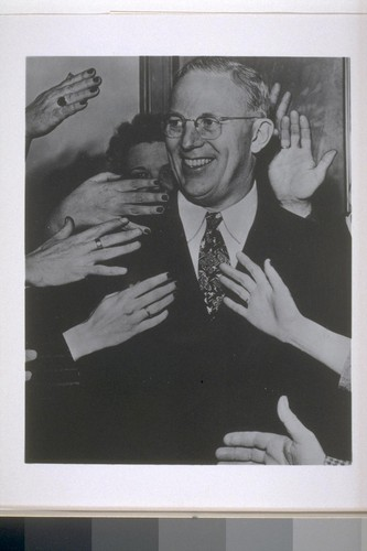 [Earl Warren surrounded by hands.]