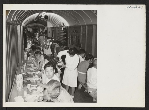 Dinner time in the improvised baggage car where transferees were fed by the Army enroute from Topaz to Tule Lake. The meals were excellent and the service, with volunteer help from among the passengers, was speedy and efficient. Photographer: Mace, Charles E
