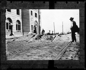 View of Mission Street in San Francisco, showing twisted streetcar tracks and other earthquake damage, 1906