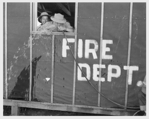 Poston, Ariz.--Site No. 1. Evacuee firemen getting drinks at this War Relocation Authority center. Frank Shibata (right).--Photographer: Clark, Fred--Poston, Arizona. 5/25/42