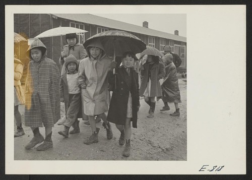 Grade school children leaving the school, at the Jerome Relocation Center. During the rainy season, in the heart of the Arkansas lowlands, the Jerome Center, whose residents are former Californians of Japanese ancestry, was one vast quagmire. Photographer: Parker, Tom Denson, Arkansas