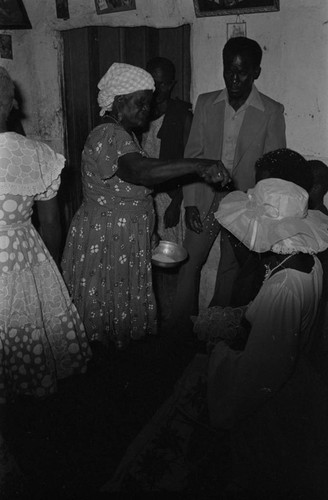Woman throwing rice at wedding couple, San Basilio del Palenque, ca. 1978