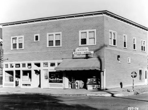 Photogrpah of a building. The shops include, Henry's Market, Santa Fe Wines, and Compton Cleaners