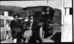 Two women on river ferry seated on front of a car with California license plates, about 1916