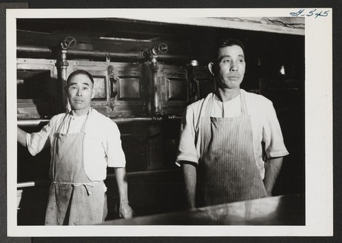 Norima Kitaoka and Yoshito Sera pose for the photographer beside one of the giant ranges in the kitchen at the