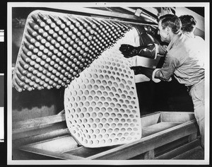 Man stripping a piece of completed c-foam from a mold at the American Latex Products Corporation, ca.1950