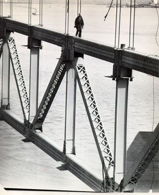 [Worker walking along a steel structure during construction of the San Francisco-Oakland Bay Bridge]