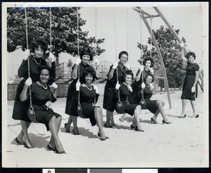 Group of African American women posing on a swingset, Los Angeles, ca. 1951-1960