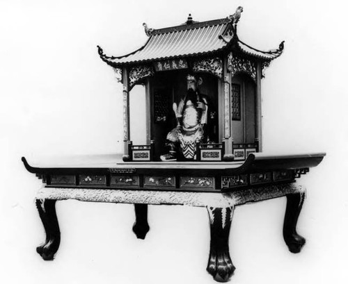 "Photograph of ""Quan Ti"" Temple Altar with Quan Dai deity. Altar was brought over from China by ""Tony"" Quan, to set up a one-room temple near his business on Spring Street"