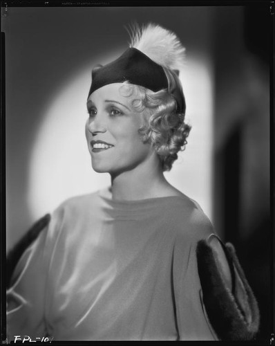 Peggy Hamilton modeling a dress with dolman sleeves and fur epaulettes and a hat, circa 1933