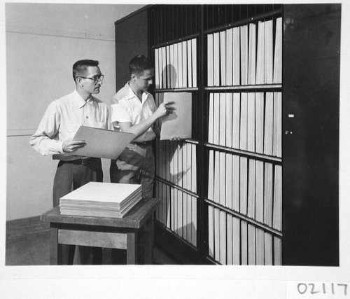 James McClanahan and Hendrik Rubingh filing sky survey plates in a vault room