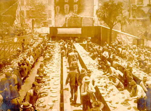 [workers sitting down for a meal in Union Square, St. Francis Hotel in background]
