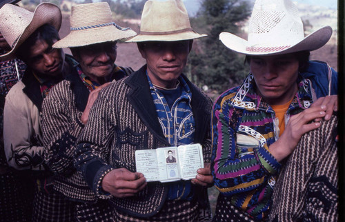 Mayan man shows his identification while in line to vote, Guatemala, 1982
