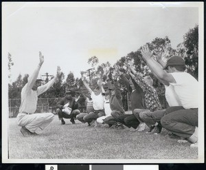 Youth stretching on playing field, Los Angeles, ca. 1951-1960