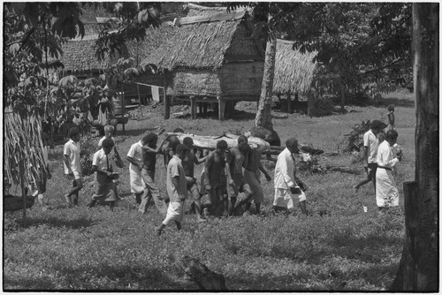 Funeral: men carry body that has been wrapped for burial, across village clearing, other men carry books (probably Bibles)