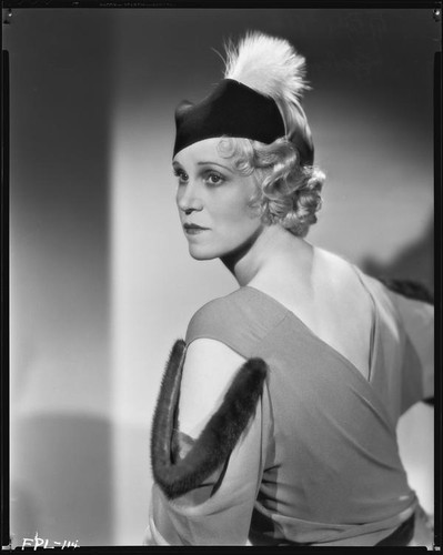 Peggy Hamilton modeling a dress with dolman sleeves and fur epaulettes and a hat, 1933
