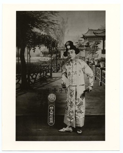 Actor in a dan role dressed in embroidered jacket and skirt holds a folding fan /