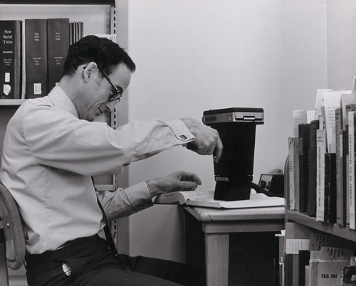 A photograph of Ray Reeder with a strange photographic device processing catalog cards