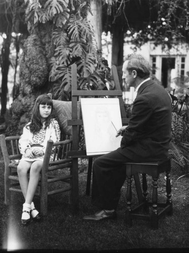 An artist paints a portrait of a little girl