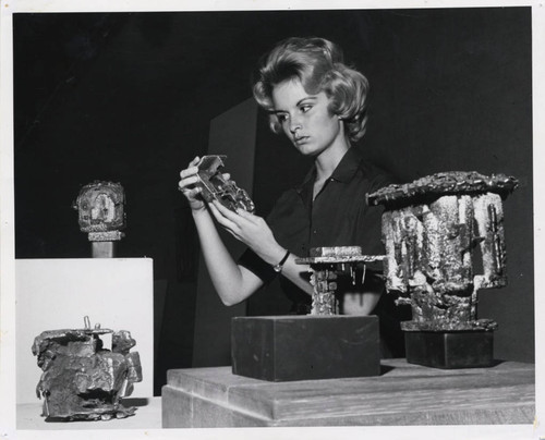 Woman examines sculpture, Scripps College