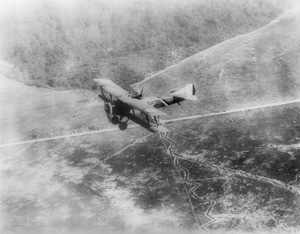 "Downward view of a ""Chateau Thierre Aeroplane"", a World War I aircraft, in flight over Argone Forest and French trenches, ca.1914-1918"
