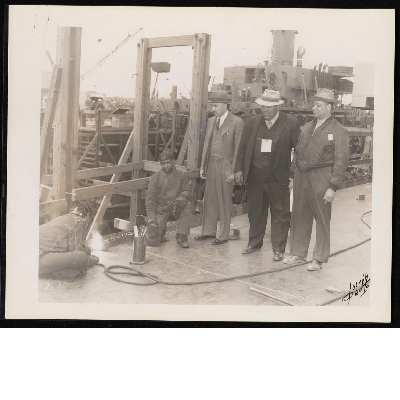 C.L. Dellums, Spencer Jordan, and Ben Watkins standing next to two welders at the Kaiser Shipyard Richmond, California