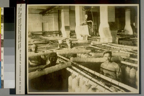 This shows Borax crystallizing tanks, the method of crystallizing and the men removing the finished product from the tanks