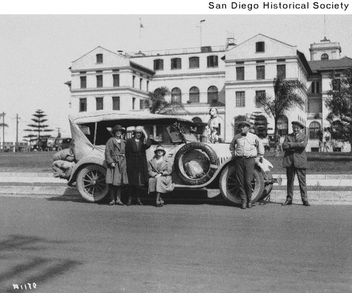 Three women and two men around an automobile parked in front of a large building