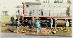 Workmen are removing the P&SR railroad tracks on South Gravenstein Highway 116 near Industrial Avenue and Sparkes Road, about 1984 with the help of a Southern Pacific engine