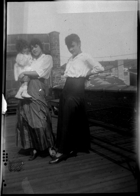 Two women and child standing on outdoor deck
