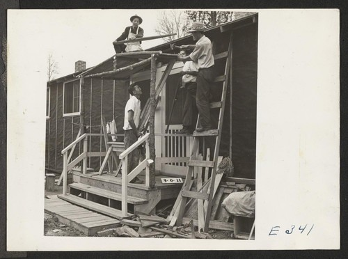 Adding a front porch to their barracks, these centerites are thinking of winter snow and rain. Photographer: Parker, Tom McGehee, Arkansas