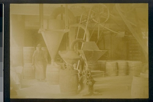 [Factory worker loading barrels.]