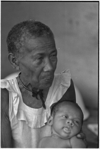 Elderly woman, Bomtavau, holding young infant, perhaps her grandchild