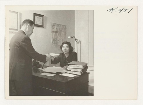 Lily Nakanishi, in San Francisco, hands an appointment slip for work to a recently returned evacuee. Lily operates an independent