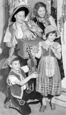 [Students Albert Landi, Adrienne Levitt, Frank Marynelli and Marie Louise McPherson of Winfield Scott Elementary dressed in costumes holding instruments]