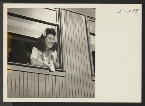 Closing of the Jerome Center, Denson, Arkansas. An attractive Miss, aboard the train for Gila River, smiles as she calls to her friends who assembled at the train to say Aloha. Photographer: Iwasaki, Hikaru Denson, Arkansas