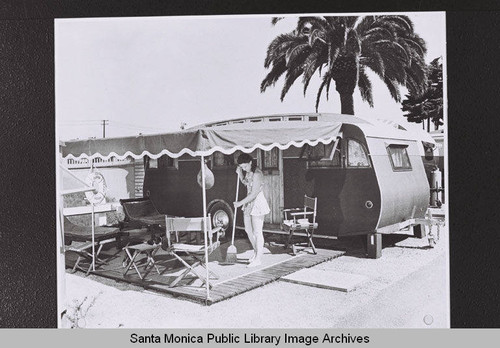 Woman sweeps the covered patio area outside her trailer in Santa Monica, part of Douglas Aircraft Company employee housing during World War II