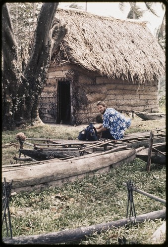 Canoes: Edwin Hutchins sits on fishing canoe, other canoes nearby, house in background