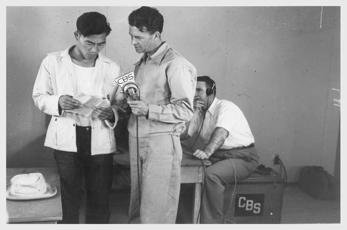 Poston, Ariz.--George Kita (left) and Norris James, WRA official, in an interview at this War Relocation Authority center during a CBS nationwide hookup.--Photographer: Clark, Fred--Poston, Arizona. 5/26/42