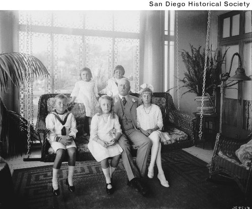 John D. Spreckels sitting on a porch swing with his grandchildren