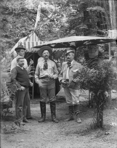 Four men standing by large paper umbrella, Bohemian Grove. [negative]