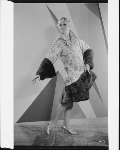 Peggy Hamilton modeling an Adrian evening wrap of brocade and mink, 1929