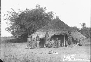 Group of African people standing in front of a hut, Makulane, Mozambique, ca. 1896-1911