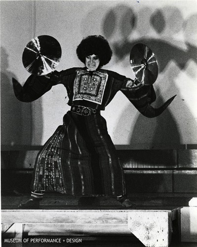 "Anna Halprin with a pair of cymbals in a performance of ""New Time Shuffle"""