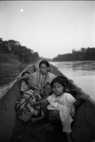 Refugee woman and three children in a canoe, Chiapas, 1983