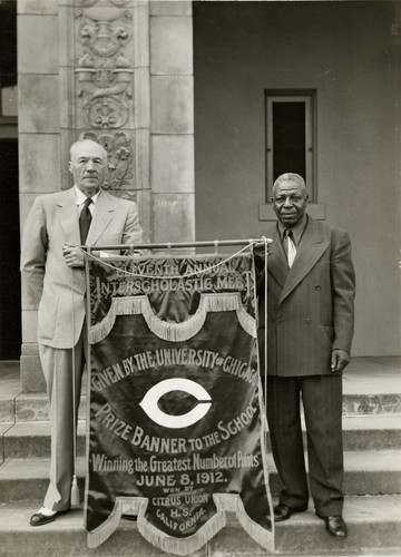 Herb Whitted and Stonewall Jackson hold replica of United States Track Championship Banner of 1912