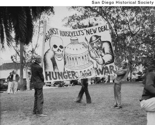 Two men holding an anti-New Deal sign at a Communist demonstration in New Town Park prior to the start of the riot