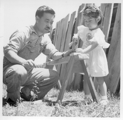 Little Mira Nakashima is following in her father's footsteps as she drives a nail into a piece of wood outside