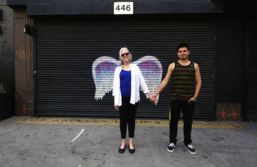 Unidentified man and woman holding hands and posing in front of a mural depicting angel wings